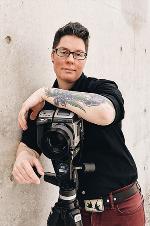 Image: A potrait of Jess T. Dugan. She is standing behind a camera facing the viewer. She wears a black shirt and glasses.