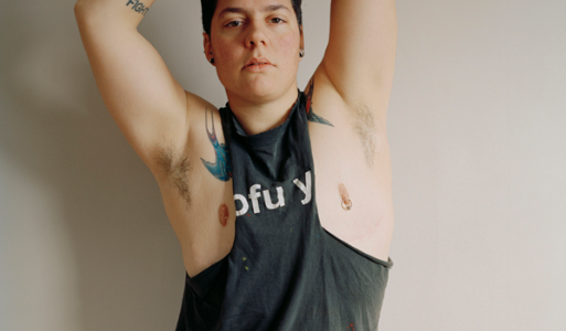 Image: Jess T. Dugan, Self-Portrait (Muscle Shirt), 2013. Self-portrait of Jess T. Dugan wearing a muscle t-shirt. She is looking forward at the viewer with her arms stretched out above her head.
