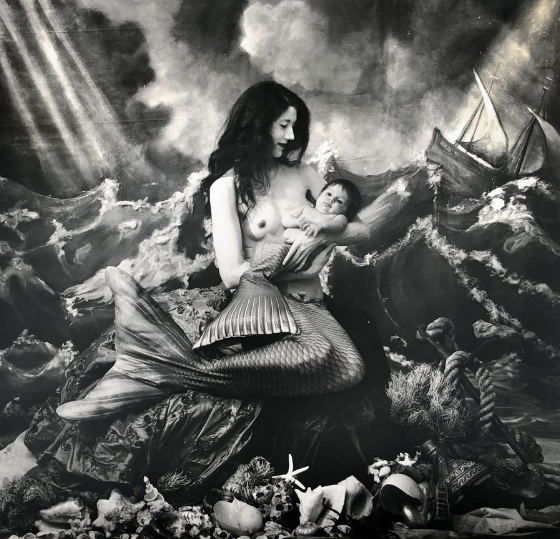 Image: Joel-Peter Witkin, A Mermaid's Tale, NM, 2018. A black and white photograph of a woman wearing a mermaid tail, seated on a seashell-ladened formation. She is bare-chested holding a baby, also adorned with a mermaid tail. Behind them is a painted backdrop depicting a sea full of waves and a ship off to the right.