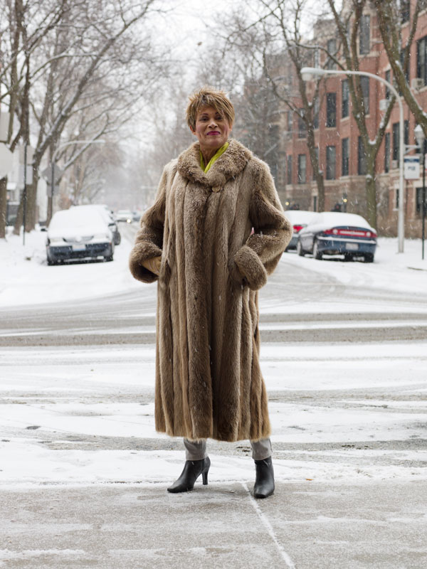 Image: Jess T. Dugan, Gloria, 70, Chicago, IL, 2016. A portrait of a person wearing a fur coat standing in a snowy street in Chicago.