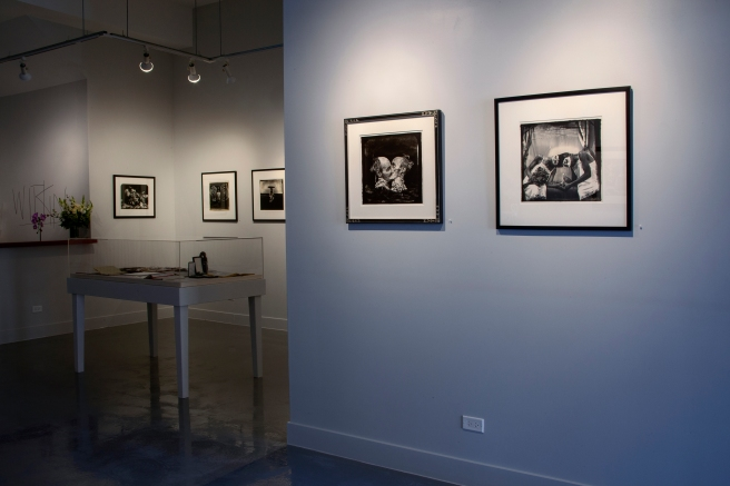 Image: A view of the inside of Catherine Edelman Gallery showcasing the work of Joel-Peter Witkin. On the wall hangs several black and white photographs.