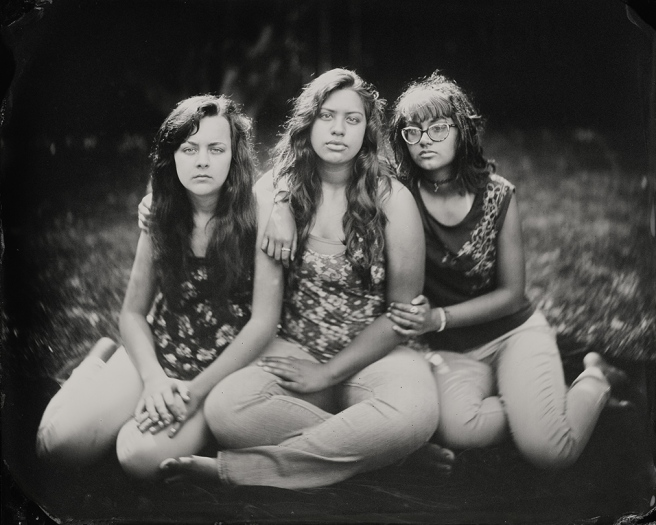 Image: Caroline, Emily, Chloe 2014 by Keliy Anderson-Staley. A black and white photograph of three teenage girls. All three of them are sitting on the ground outside facing the viewer. They are not smiling, but embrace each other.
