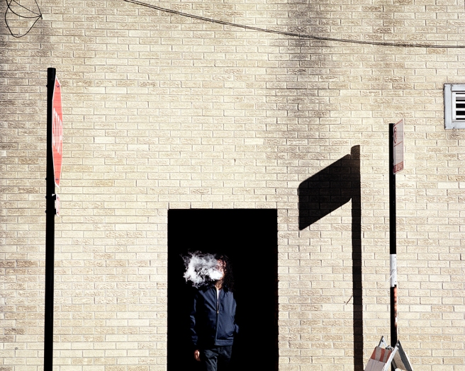 Image: Emerge, 2017 by Clarissa Bonet. A person wearing navy blue walks out of a pitch-black doorway while blowing cigarette smoke. The person is surrounded by the outside wall of the building, which is a light beige brick. There is a stop sign to the left and a no parking sign to the right. Stark shadows enter the frame.