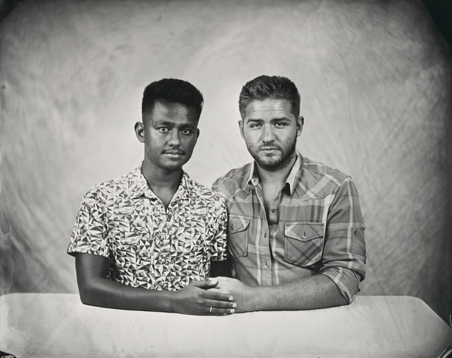 Image: Rajab and Laramie, 2018 by Keliy Anderson-Staley. A black and white photograph of two young men sitting at a table. The man on the left is wearing a patterned shirt and has dark hair and complexion. The man on the right has medium-colored hair and a light complexion. He wears a plaid shirt. The two men are holding hands and looking straight out at the viewer.