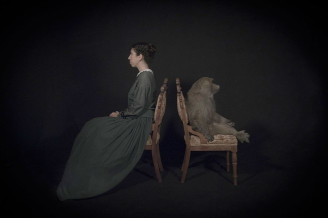 Image: Tami Bahat, The Dispute, 2016. A photograph of a woman in a Victorian-style, gray-blue dress sits on a chair facing left. to her right, a monkey sits in a chair facing right. They are sitting back to back.