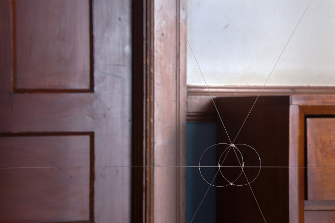 Image: Dresser, 2015 by Bill O'Donnell. A photograph that is cropped so that it shows the wooden frame of a door, a wooden door, and the left side of a wooden dresser. There are three lines on dissecting the photograph: one from left to right, and the other going diagonal from top to bottom. There are two circles connecting these intersecting lines.
