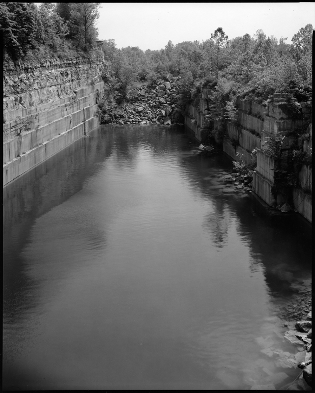Image: Empire State Quarry, Oolitic, 1983 by Jeffrey Wolin. A black and white photograph of a swimming hole. There are stone walls to the left and right of the water, with trees surrounding it. There is a pile of rubble at the end of the quarry towards the upper center of the frame.