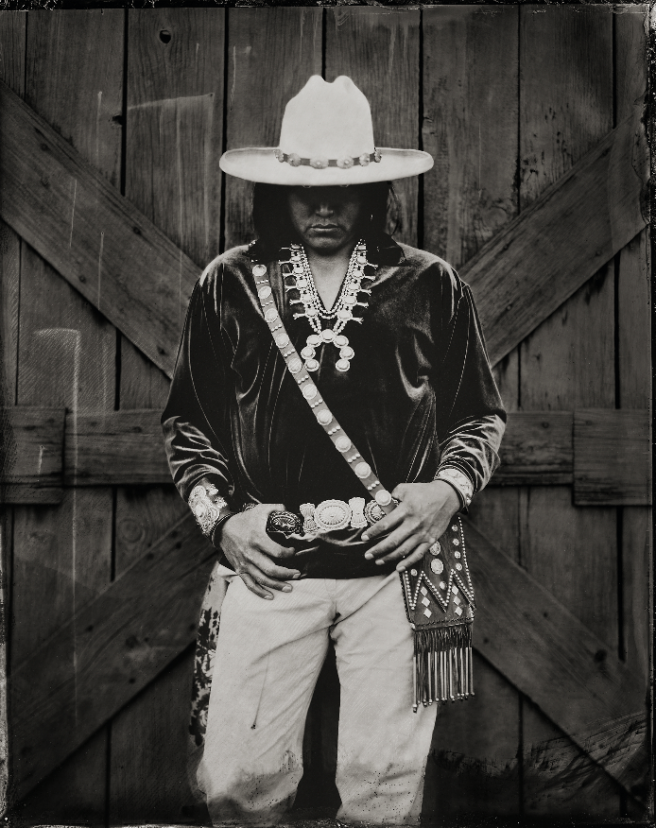 Image: Navajo Cowboy, October, 2018 by Joseph Kayne. A black and white photograph of a Navajo man wearing traditional, native dress. He is standing in front of wooden siding with his hands resting on his belt buckle. His head is tilted slightly downward so that he eyes are slightly covered by his hat.