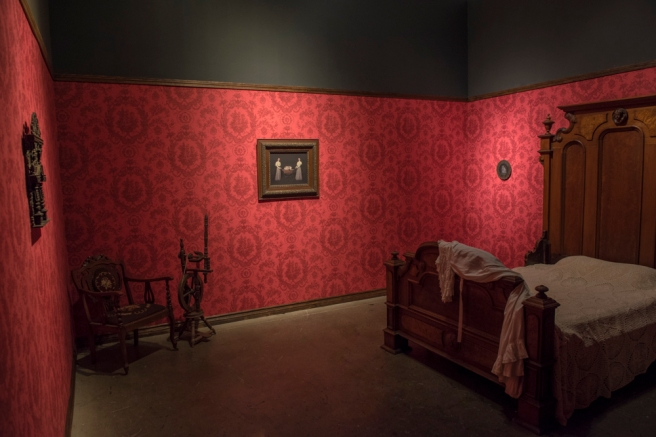Image: An installation of a past exhibition of Tami Bahat's work. The room has bright red, patterned walls where three photographs with vintage frames hang. There is a chair and a bed in the room that are of the Victorian period.