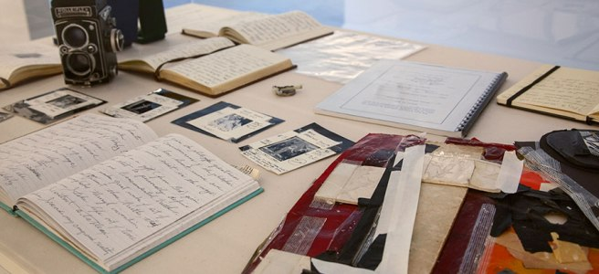 Image: Journals, cameras, and other ephemera from Joel-Peter Witkin lay on a display table as part of the exhibion Joel-Peter Witkin: From the Studio, 2019..