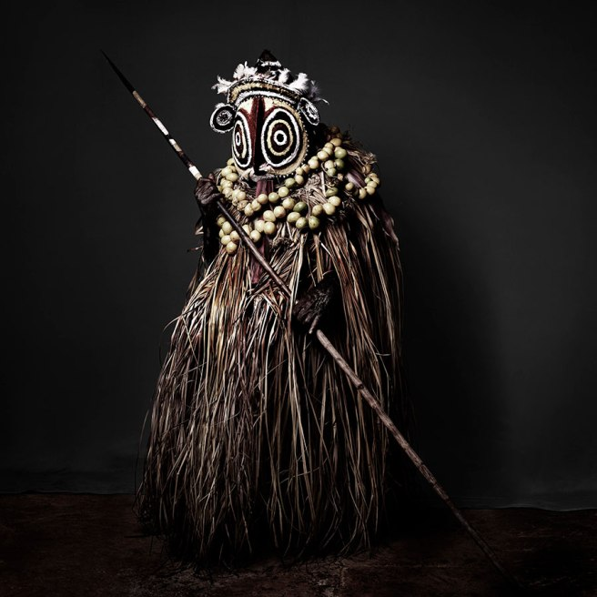 Image: Sandro Miller, Aluseki in the Tumbon Costume of the Abelum Tribe, 2016. I native person of Papua New Guinea stand in front of a grey background while holding spear. Their face and body are completely covered with traditional clothes. They are wearing a mask.