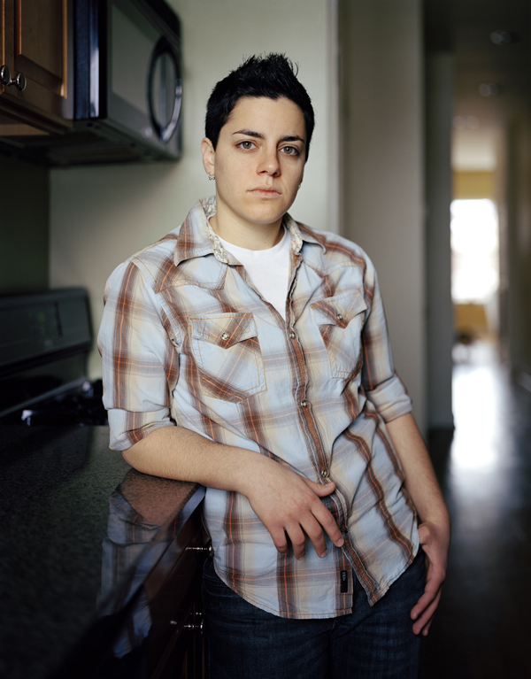 Image: Jess T. Dugan, Betsy, 2013. Betsy is stand, leaning on a countertop Betsy is facing the viewer and wearing a plaid shirt.