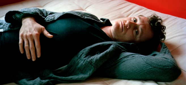Image: Jess T. Dugan, Dallas Lying on the Bed , 2012. Dalls lays on a white mattress looking at the viewer. He is wearing all dark clothing with one hand on his stomach. The wall behind him is bright red.