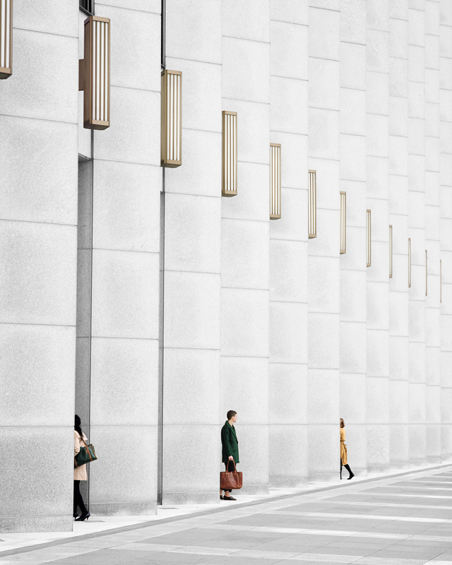 Image: Clarissa Bonet, Fortress, 2016. A photograph showing the side of an off-white building. There are three people in the composition that walk to and from the building.