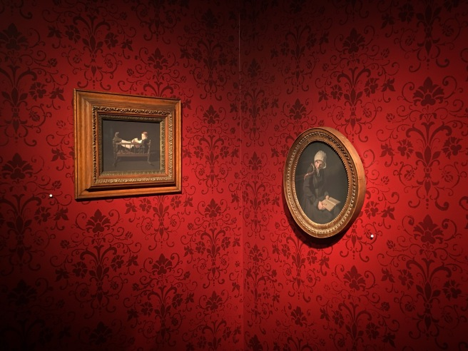 Image: Two photographs in vintage frames hang on a red wall. The red wall has a dark red vintage, wall-paper-like pattern.