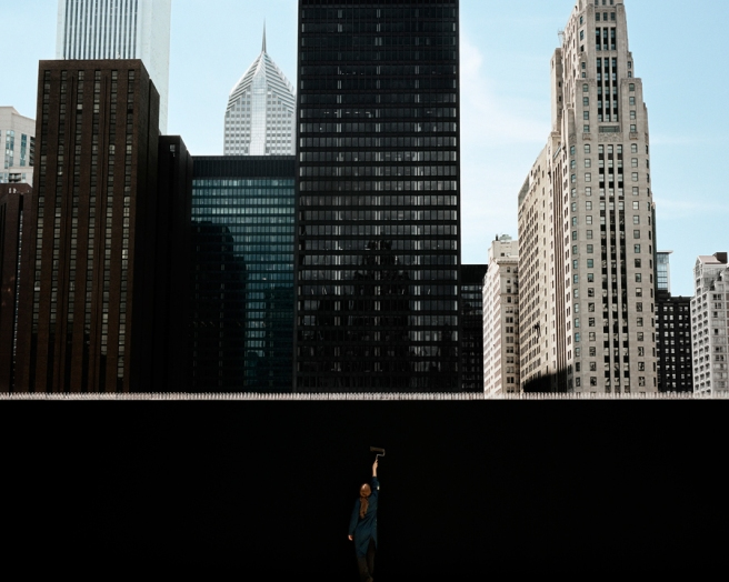 Image: Clarissa Bonet, In Progress, 2016. A photograph of the skyline of Chicago in the background. In the foreground, there is a woman painting a wall. The wall is completely black.