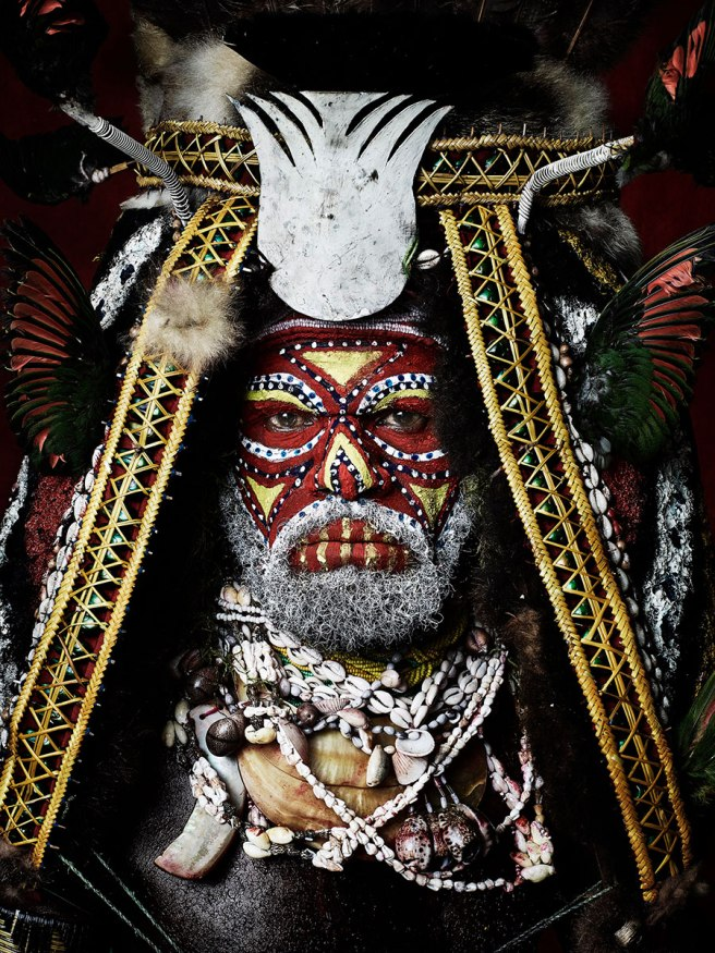 Image: Sandro Miller, James Botol of the Kuruwari Tribe, 2015. I native person of Papua New Guinea is looking straight at the viewer. The composition is cropped close to his face. He is wearing red and yellow facepaint and a large head piece.