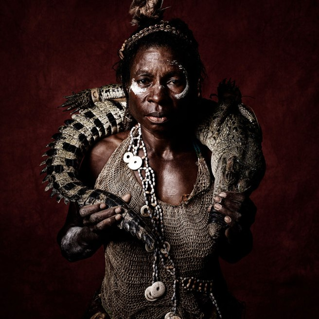 Image: Sandro Miller, Quentin Daki of the Nowra Tribe (Crocodile Around Neck), 2016. A woman stands in front of a maroon background facing the viewer. She is holding a small crocodile around her neck and wearing traditional garb.