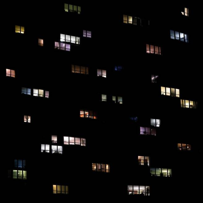 Image: Clarissa Bonet, SL.2018.0222, Chicago, 2018. The photo is predominantly black, with different colored light radiating from windows.