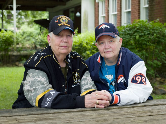Image: Hank, 76, and Samm, 67, Little Rock, AR, 2016. A photographic portrait of two nongender conforming adults. They both wear sports jackets and hats and sit facing the viewer while holding hands.