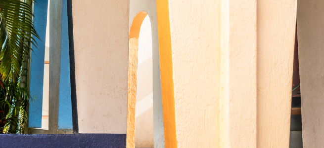 Image: Jim Ferguson, Todo Santos 2, 2019. Exterior view of a beige building with yellow accents. The building has several arches and a green plant sits to the left side of the frame.