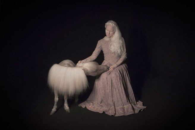 Image: Tami Bahat, The Resemblance, 2017. I photo of a woman with long, white hair petting a small, white pony with similar hair. The woman is wearing a long, Victorian style, salmon colored dress. The background is all black.