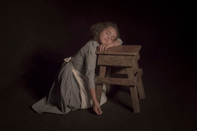 Image: Tami Bahat, The Slumber, 2017. A photograph of a young girl sleep while leaning against a stool. She is wearing a pale blue dress with a white apron.