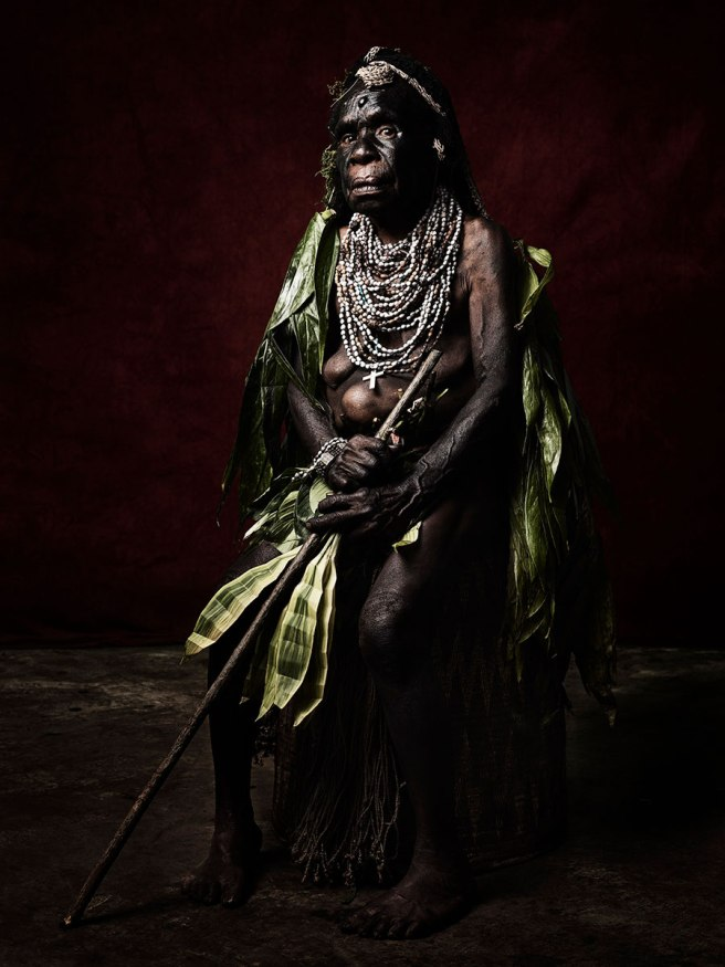 Image: Sandro Miller, Agnes Nung of the Warawau Tribe, 2017. A woman from Papua New Guinea sits facing the viewer. She is wearing traditional dress and sits in front of a maroon background.