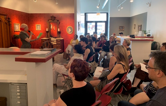 Image: A crowd sits at Catherine Edelman Gallery facing the left side of the frame. They are facing a woman reading poetry.