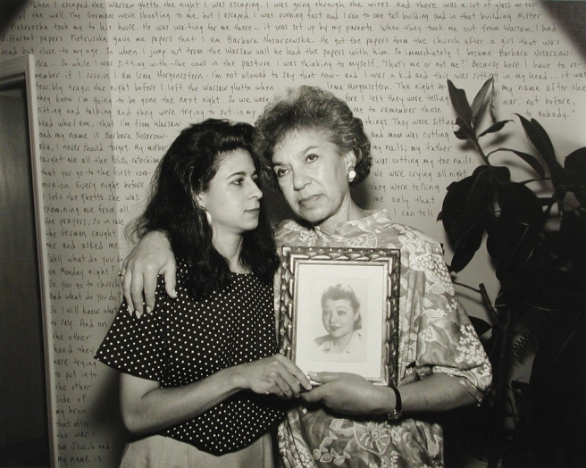 Image: Jeffrey Wolin, Irma Morgenztern, b. 1933, Warsaw, Poland, 1992/94. From the Portraits of the Holocaust series. Two women embrace each other while holding a photograph of a loved one. The wall behind them contains text.