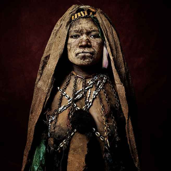 Image: Madeleine Eliza of the Ubura Village, 2015 by Sandro Miller. A photograph of a woman from Papua New Guinea. She wears a brown veil with shell jewelry drapped around her neck.