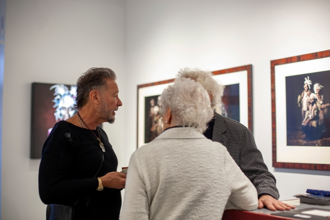 Image: Sandro Miller discusses his artwork with two men. They stand in front of a light grey wall with photographs of people from Papua New Guinea being displayed.