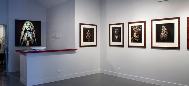 "Image: View of the exhibition ""Sandro Miller: I am Papua New Guinea."" A row of photographs of people from Papua New Guinea are hung on a light gray wall. There is a desk on the left side of the frame."