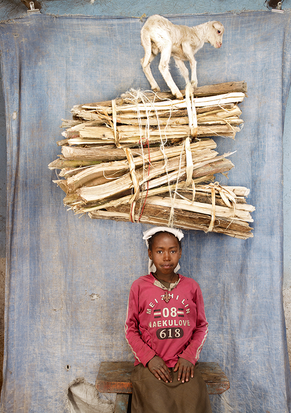 Image: Floriane de Lassée, Aru, Ethiopia, 2012. A photo of a child balancing a pile of wood on her head along with a goat. She sits in front of a blue background.