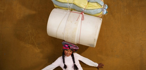 Image: Floriane de Lassée, Celia, Bolivia, 2013. A photo of a girl balancing her posessions on her head, which include two barrels and a pillow. She is wearing a white shirt, a green skirt, and braids. She stands in front of a tan wall.
