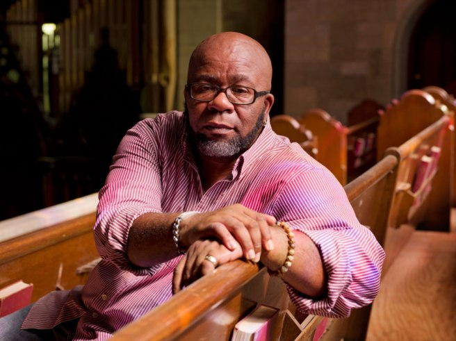 Image: Jess T. Dugan, Louis, 54, Springfield, MA, 2014. A portrait of a person wearing a pink shirt and glasses, sitting on a church pew.