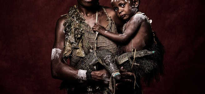 Image: Sandro Miller, Milfred and Bridget of the Nowra Tribe, 2016. I citizen of Papua New Guinea is standing facing the viewer while holding a small child. They are both wearing traditional dress.