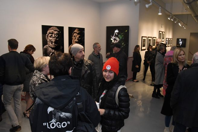"Image: A crowd of people looking at Sandro Miller's exhibition ""I am Papua New Guinea"" at Catherine Edelman Gallery."