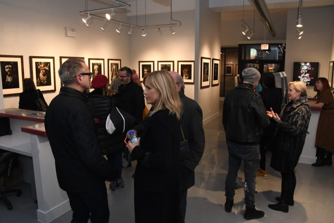 "Image: A crowd of people at Catherine Edelman Gallery looking at the exhibition ""Sandro Miller: I am Papua New Guinea."""