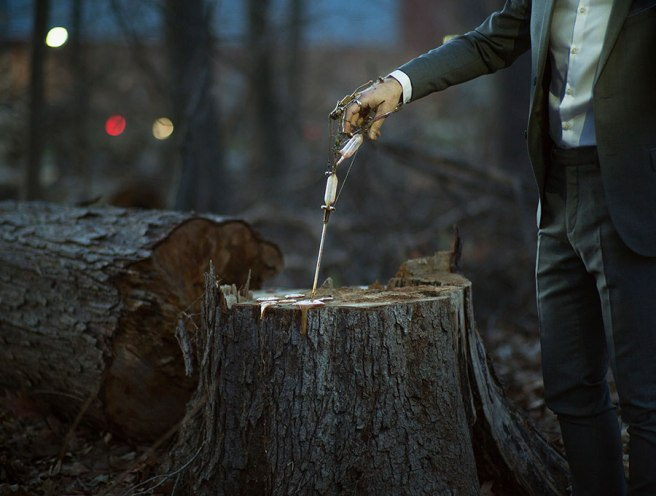 Image: Robert & Shana ParkeHarrison, Reparation, 2017. A man in a suit holds a hand held contraption up to a tree stump.