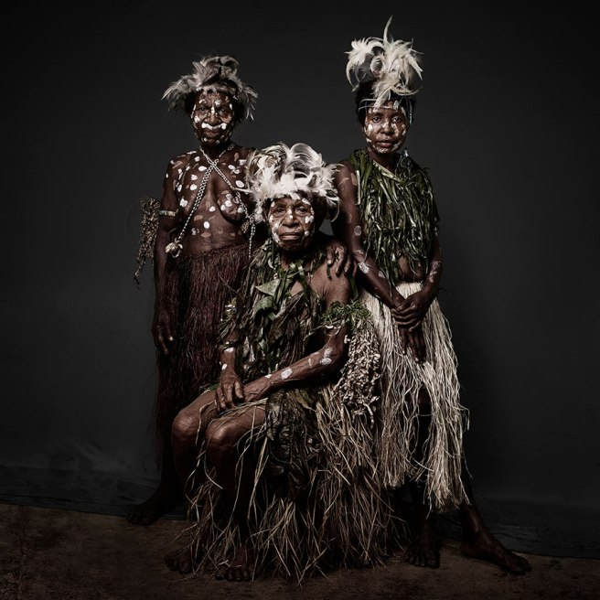 Image: Sandro Miller, Rosa, Alberta, and Augusta of the Buki Village, 2016. Three women who are citizens of Papua New Guinea are facing the viewer while wearing traditional clothing. Two are standing while the person in the middle is sitting. They all have on white face and body paint.