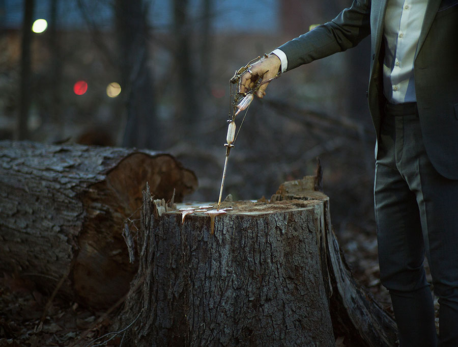 Image: Reparation, 2017 by Robert & Shana ParkeHarrison. A man holds a contraption spewing brown liquid onto a tree stump.